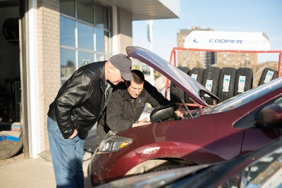 photo of the owner of Market Mall Auto Repair showing a customer how to maintain his vehicle
