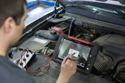 photo of technician using computer to diagnose engine problems